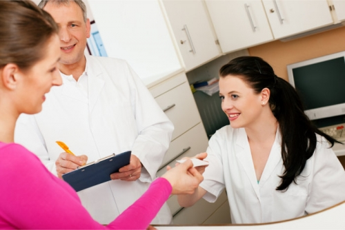 lady handling her health insurance card to a nurse while the doctor is writing on a clipboard