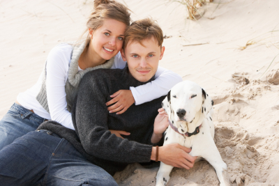 Romantic Teenage Couple On Beach With Dog